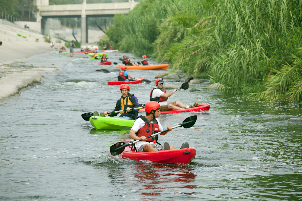Kayakers stretched out along the LA River behind George Wolfe, leading LA River Expeditions. On Memorial Day, the Los Angeles River Pilot Recreational Zone officially opened to the public for kayaking, walking, birdwatching, and fishing along a 2.5 mile stretch of the river in the Elysian Valley.