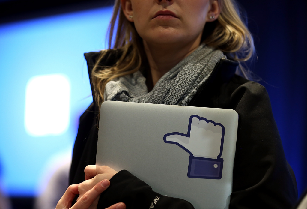 MENLO PARK, CA - APRIL 04:  A Facebook employee holds a laptop with a