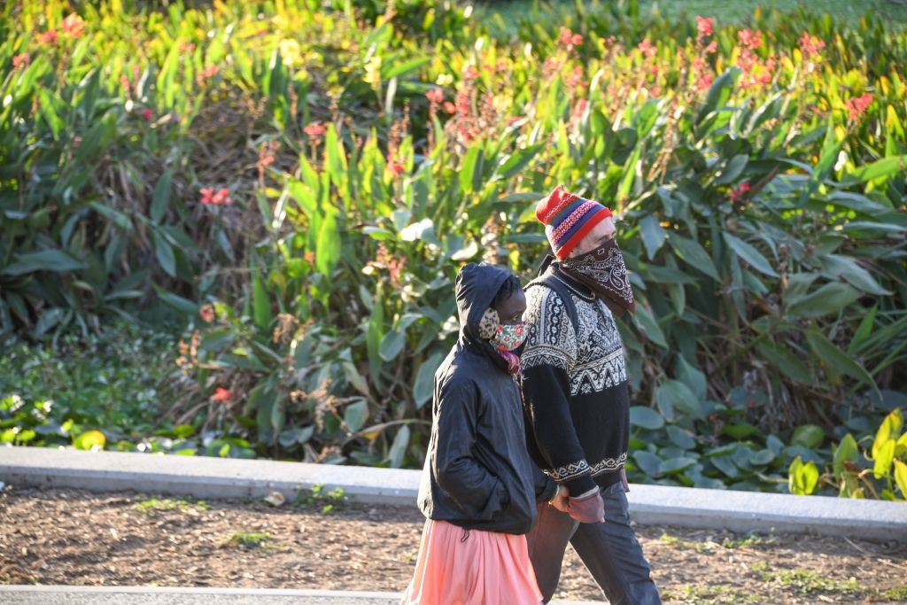 Two people wearing face coverings to prevent the spread of coronavirus walk in a park, November 9, 2020 in Los Angeles, California.