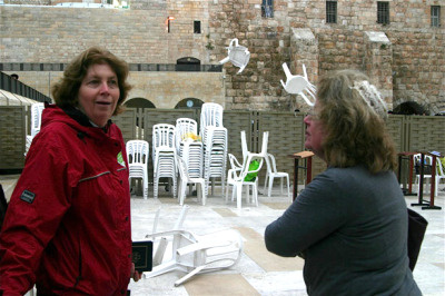 Anat Hoffman of Women of the Wall laughs as ultra-Orthodox men throw chairs over the separation screen at the Western Wall as the women prepare to pray. It is a felony for women to pray aloud in a group, wear a prayer shawl and read the Torah at the Western Wall because it is considered offensive to the Orthodox rabbinate which governs the site.