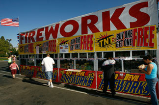 Customers buy fireworks for upcoming July 4th celebrations from the Rotary Club of Fillmore Sunrisers fireworks stand on June 30, 2008 in Fillmore, California.