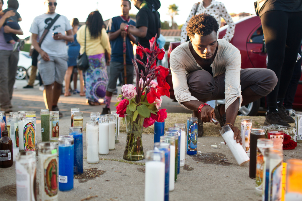 Malcolm McIntosh lights candles at a memorial where Los Angeles police fatally shot Ezell Ford.  The LAPD inspector general is having a hard time finding witnesses.