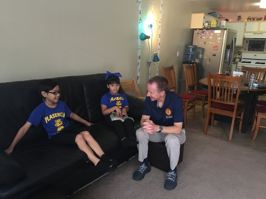 L.A. Unified School District superintendent Austin Beutner speaks with third grader Ricardo Morales (left) and first grader Lilly Morales during a home visit meant to tout the district's newly-expanded attendance push.