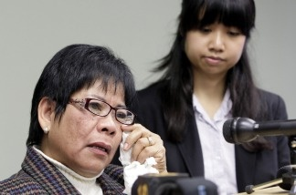 Elmora Cayme, left, reacts during a news conference on Dec. 7, 2010, where she and dozens of hospital workers in California filed suit against their employer, Delano Regional Medical Center, alleging they were the sole ethnic group targeted by an English-only rule. At right is attorney Carmina Ocampo.