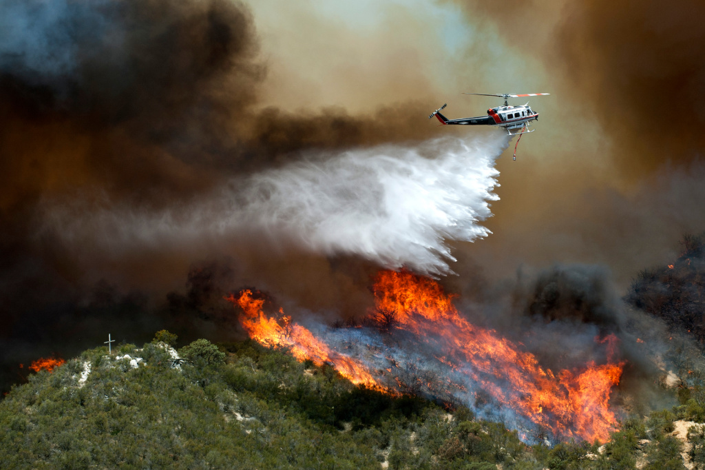 A helicopter drops water over flames in Angeles National Forest. Three days ago a fire broke out in Valencia, miles away from the Powerhouse Fire.