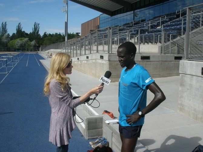 Guor Marial speaks with KNAU'S Janice Baker at the Northern Arizona University track in Flagstaff, Ariz.