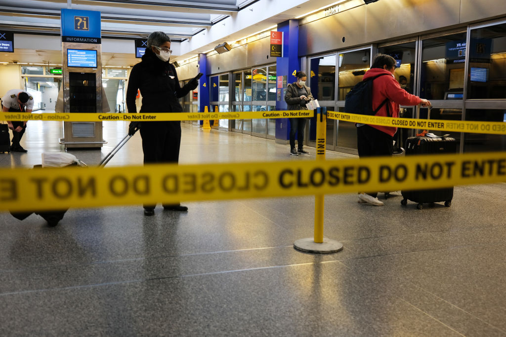 Travelers, some in protective gear, walk through John F. Kennedy Airport (JFK) as it stands mostly empty due to the ongoing cutbacks in travel because of the coronavirus.