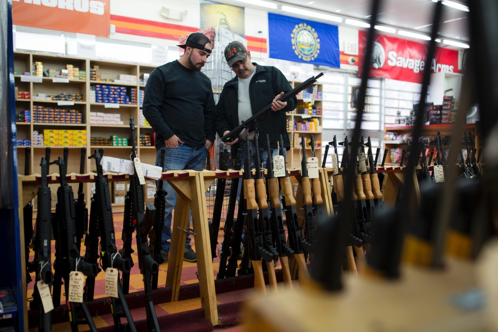 Customers look at a long gun at a gun shop on November 5, 2016, in Merrimack, New Hampshire.
