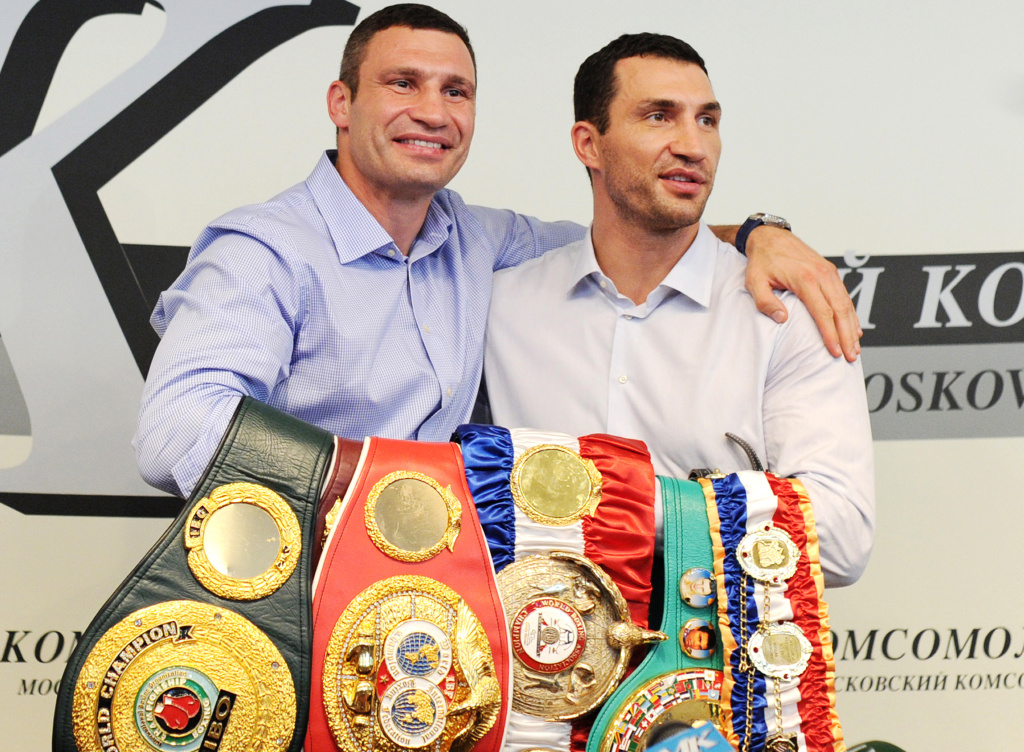 Ukrainian heavyweight boxers Wladimir Klitschko (R) and his brother Vitali Klitschko (L) pose with title belts during a press conference in Moscow, on July 8, 2011.