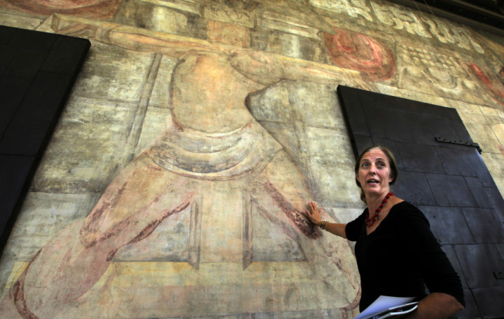 This Oct. 4, 2012 photo shows Leslie Rainer, project specialist and painting conservator at the Getty Conservation Institute, standing by the 1932 David Alfaro Siqueiros mural,