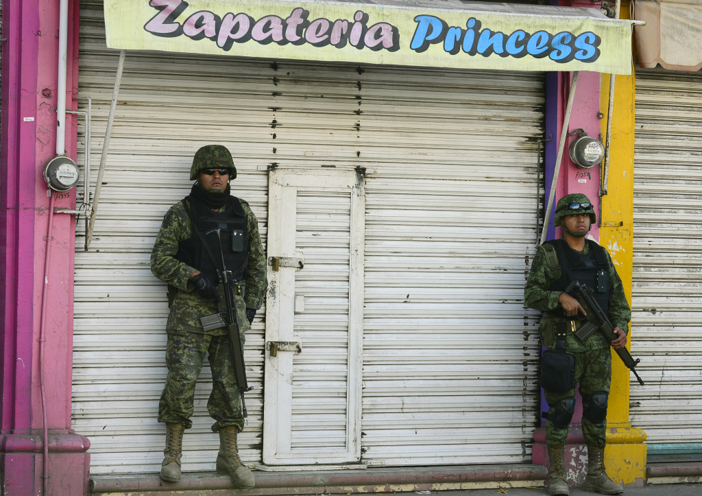 Mexican soldiers patrol the streets of Apatzingan, in Michoacan State, Mexico, on January 16, 2014.  The turmoil in Michoacan has become the biggest security challenge for President Enrique Pena Nieto's 13-month-old administration, undermining his pledge to reduce drug violence.