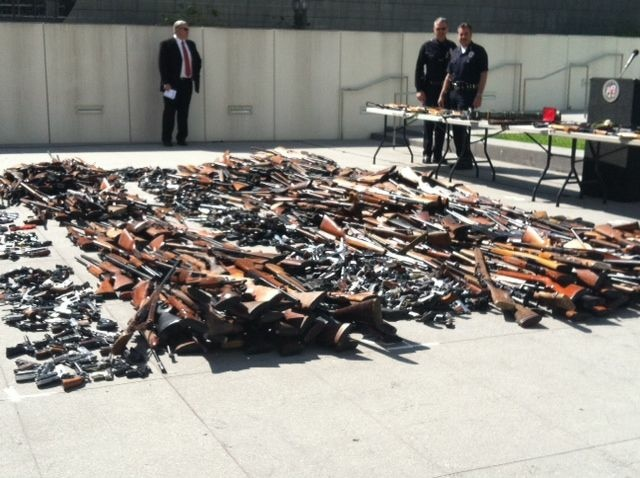 Police Chief Charlie Beck looks at the 1,673 weapons collected during the city's fourth annual gun buyback program.