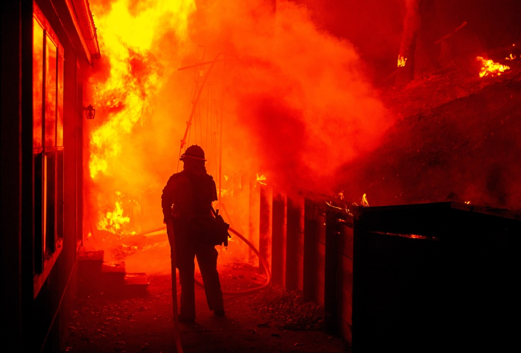 Firefighters attempt to save a burning house during the Valley Fire in Seigler Springs, California on September 13, 2015. The governor of California declared a state of emergency Sunday as raging wildfires spread in the northern part of the drought-ridden US state, forcing thousands to flee the flames. The town of Middletown, population 1,300, was particularly devastated by the Valley Fire, according to local daily Santa Rosa Press-Democrat, which said the fire grew from 50 acres to 10,000 over just five hours Saturday -- before quadrupling in size overnight.