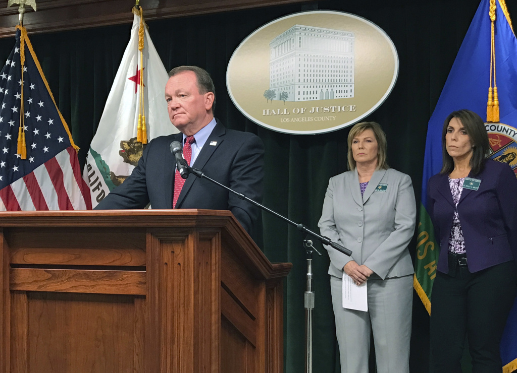FILE - In this Sept. 14, 2017 file photo Los Angeles County Sheriff Jim McDonnell announces the arrest of a deputy accused of sexually assaulting two female inmates during a news conference in downtown Los Angeles. Prosecutors say 31-year-old Giancarlo Scotti was charged Wednesday, Feb. 21, 2018, with six felony counts of sexual activity with a detainee.