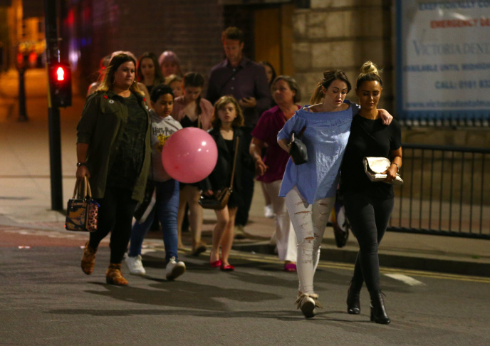 Members of the public are escorted from the Manchester Arena on May 23, 2017 in Manchester, England.