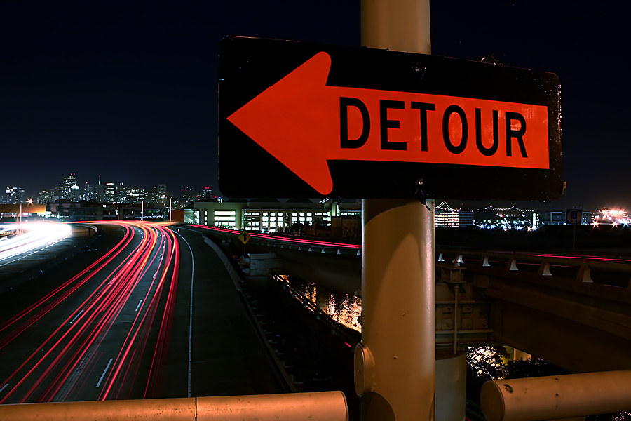 File photo of detour sign over freeway at night.