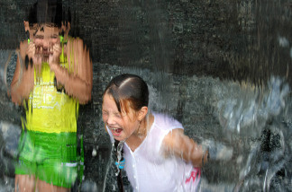 Children try to beat the heat by playing in a fountain.