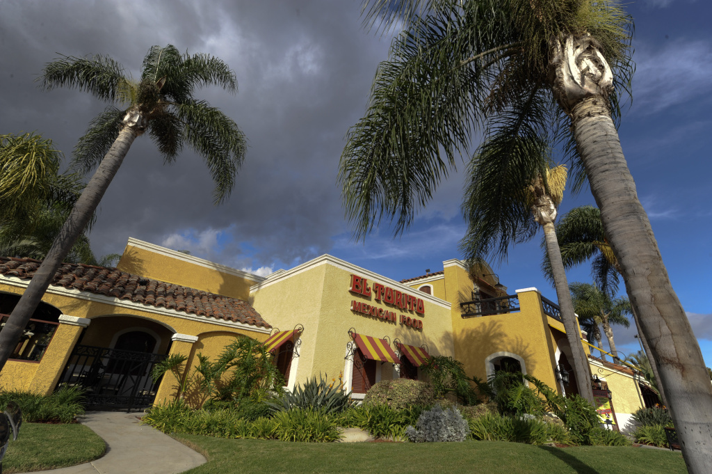 Palm trees frame the entrance to a El Torito Restaurant in Cypress, Calif., in this file photo taken Tuesday, Oct. 4, 2011. El Torito founder Larry Cano, who helped popularize Mexican food with the U.S. masses, has died at age 90.