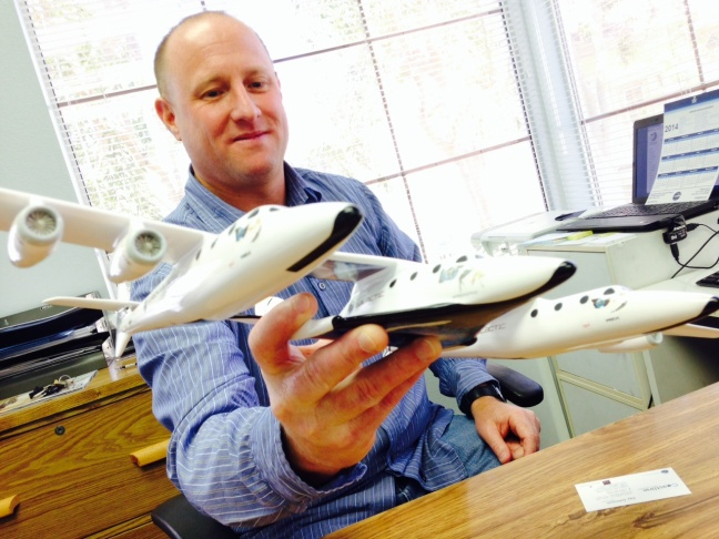 Travel agent Jay Johnson holds a model of the ship Virgin Galactic plans to use to take tourists into space.