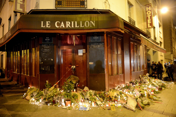 PARIS, FRANCE - NOVEMBER 14:  A boy lights candles outside Le Carillon bar, the day after a deadly attack on November 14, 2015 in Paris, France. At least 120 people have been killed and over 350 injured, 99 of which seriously, following a series of terrorist attacks in the French capital.  (Photo by Antoine Antoniol/Getty Images)
