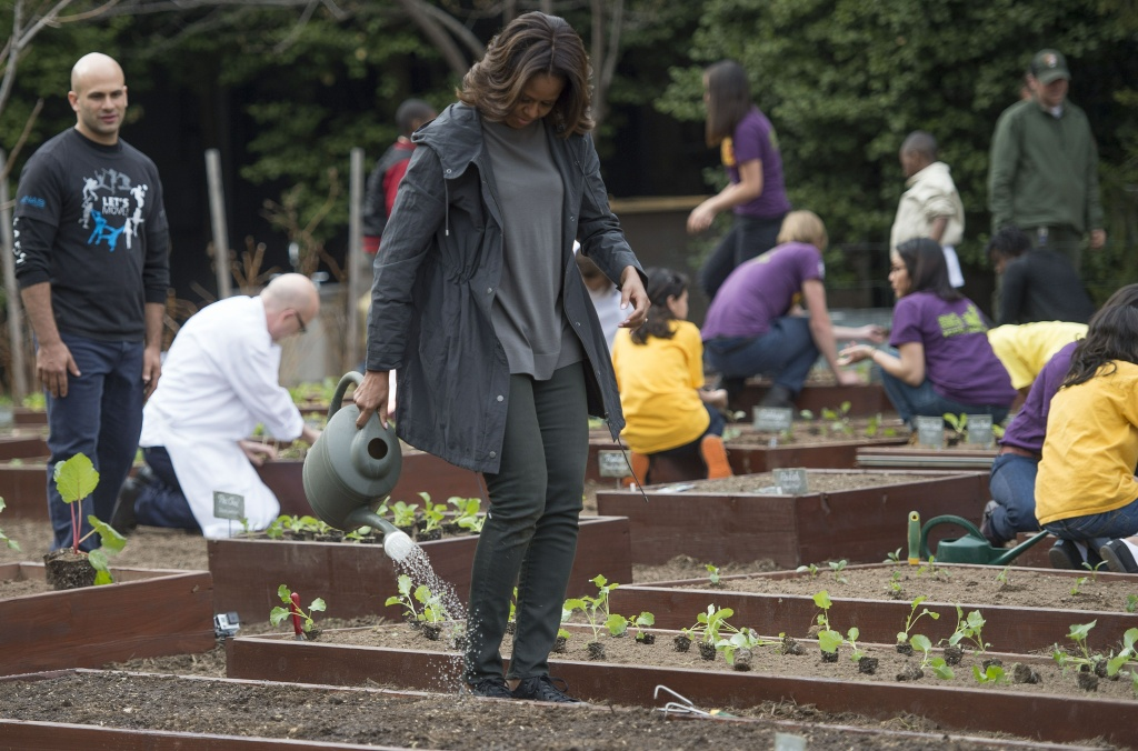 White House Senior Policy Advisor for Nutrition Policy Sam Kass and US First Lady Michelle Obama plant the 6th annual White House Kitchen Garden at the White House in Washington, DC, April 2, 2014.