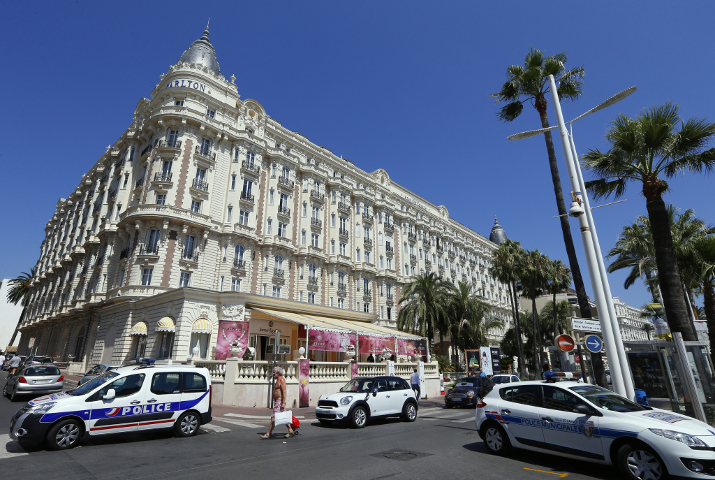 Police cars parked outside the Carlton Hotel Sunday in the French Riviera resort of Cannes after an armed man held up the jewelery exhibition 'Extraordinary diamonds.'