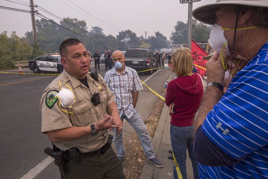 An officer talks to people who had been hoping to be escorted to pick up possessions from their homes inside an evacuation zone on October 11, 2017 in Napa, California.