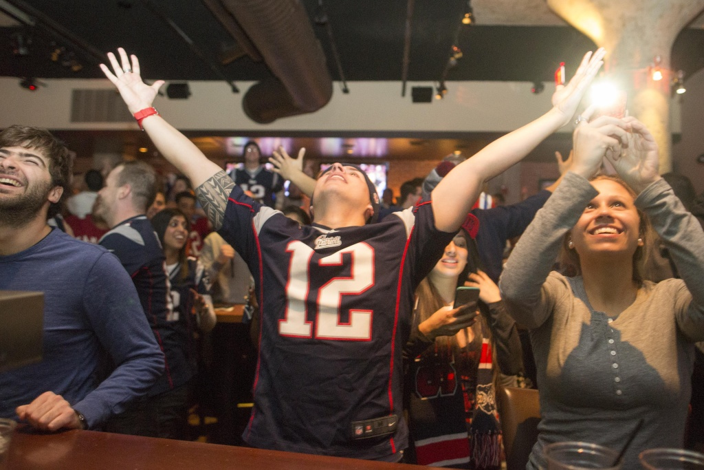New England Patriots fans cheer after the  Patriots defeated the Seattle Seahawks in Super Bowl XLIX at Jerry Remy's Sports Bar February 1, 2015 in Boston, Massachusetts.