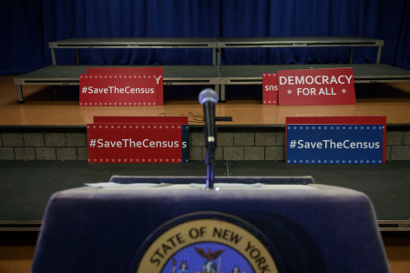 Signs sit behind the podium before the start of a press conference with New York Attorney General Eric Schneiderman to announce a multi-state lawsuit to block the Trump administration from adding a question about citizenship to the 2020 Census form, at the headquarters of District Council 37, New York City's largest public employee union, April 3, 2018 in New York City