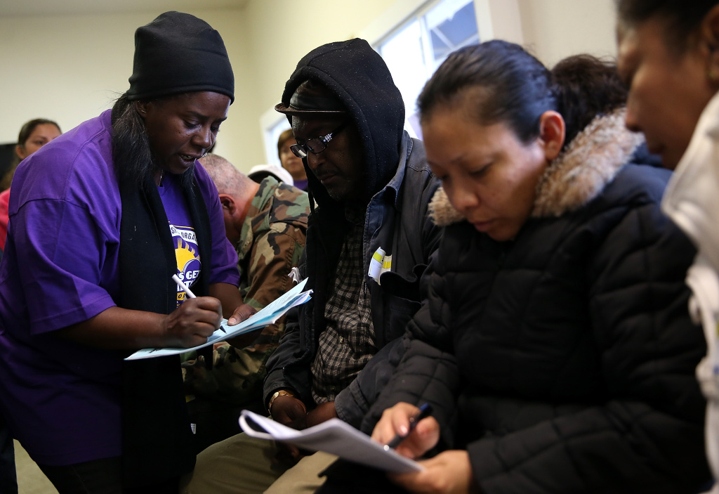 A worker helps an applicant fill out paperwork during a healthcare enrollment fair at the Bay Area Rescue Mission on March 31, 2014 in Richmond, California. SEIU-United Healthcare Workers West (SEIU-UHW) held the fair to help people sign up for free and low-cost health coverage through Medi-Cal or Covered California on the final day before the sign-up deadline.