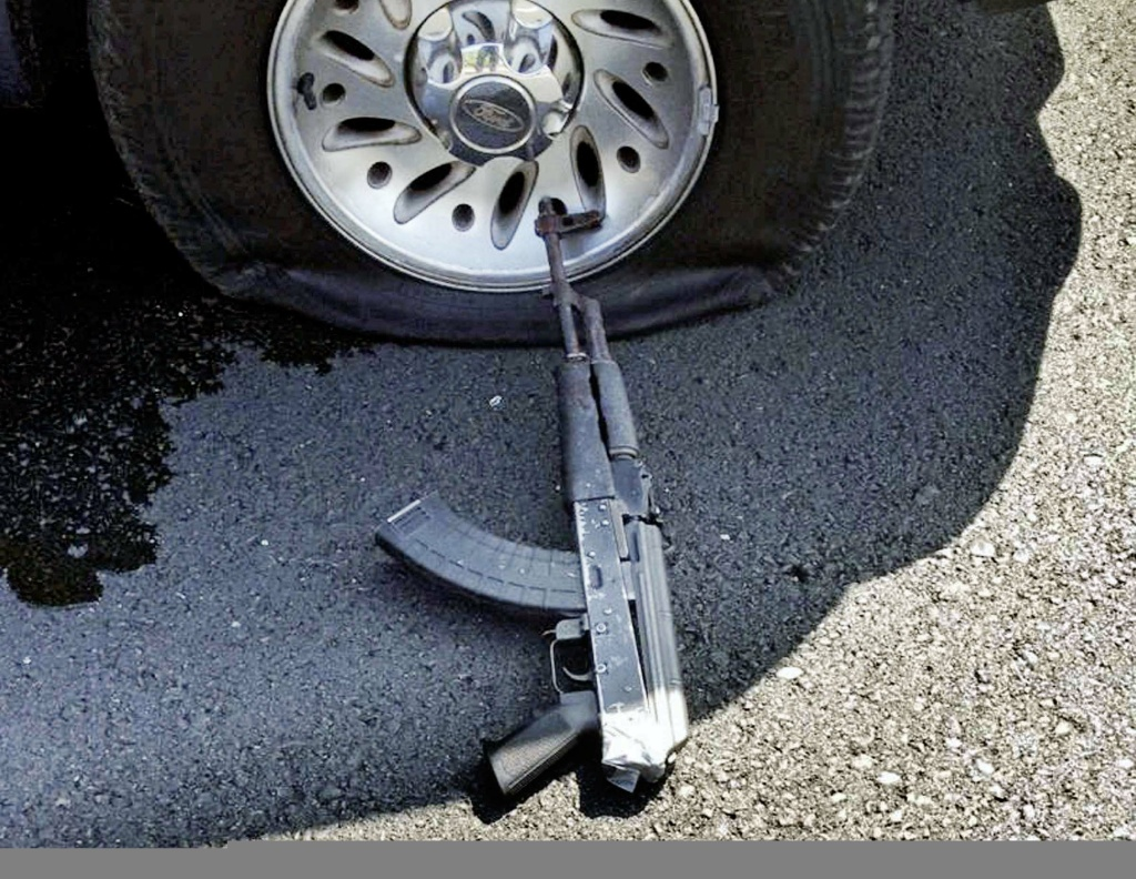 This photo provided by the Stockton Police Department shows a shot tire and firearm from the scene of a bank robbery Wednesday, July 16, 2014, in Stockton, Calif. Robbers fleeing a Stockton, California, bank took three women hostage and threw two of them from their getaway vehicle, as they fired repeatedly at police during a high-speed chase. Police shot out their tires but the shooting continued, fatally wounding two suspects and the last hostage.