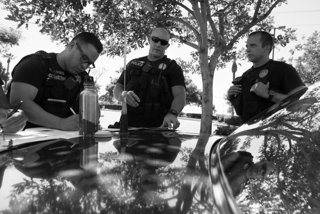 Officer Decoudres, Sergeant Corbett and Officer Adcox plan their entry into a home in Corona, Calif.