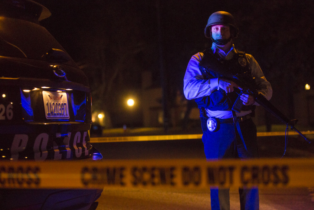 Redlands Police stand on Center Street near Pine Avenue on Wednesday night, Dec. 2, 2015 as authorities serve a search warrant following a mass shooting inside the the Inland Regional Center in San Bernardino on Wednesday, Dec. 2, 2015.