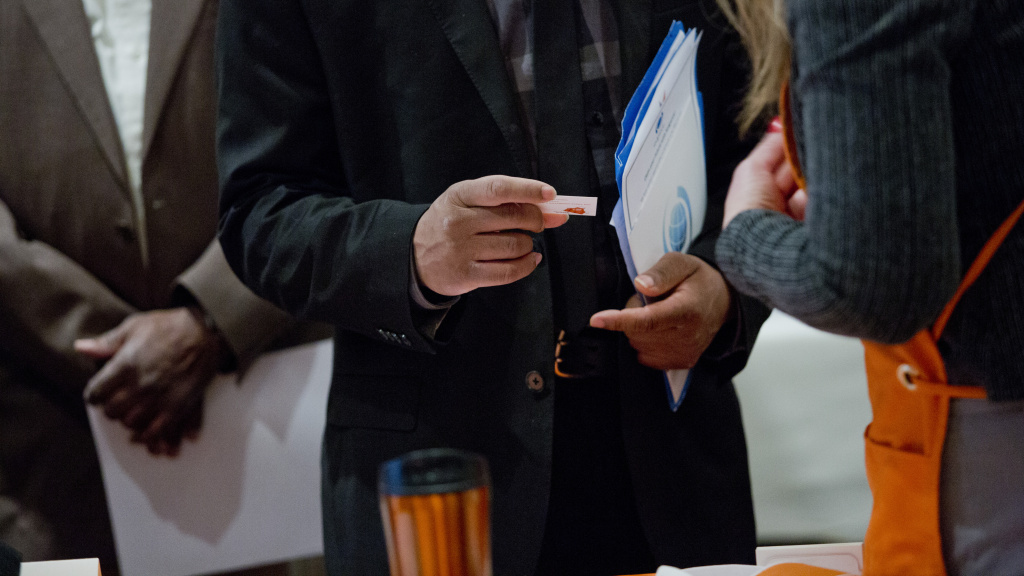 A job seeker views a business card during a Giant Job Fair in Detroit on Wednesday, Dec. 30, 2015. The Bureau of Labor Statistics reports that the U.S. economy added 292,000 jobs in December.