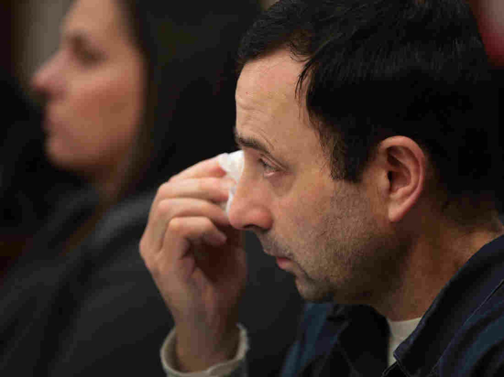 Larry Nassar wipes a tear as he listens to a young woman deliver a victim impact statement at his sentencing hearing on Wednesday. Nassar has pleaded guilty to sexually assaulting seven girls but the judge is allowing more than 100 of his accusers to speak.