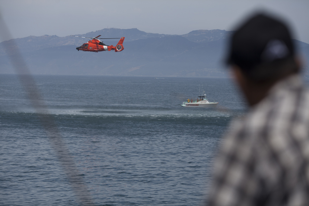 In this file photo, the U.S. Coast Guard performs rescue drills as fishermen look on from the Venice pier a day after a lightning storm killed one person in the ocean nearby. Boats from the Coast Guard and Baywatch, along with helicopters from Los Angeles and San Diego on Monday were assisting in the search for a disabled 17-foot boat that was headed from Catalina Island to Rancho Palos Verdes.