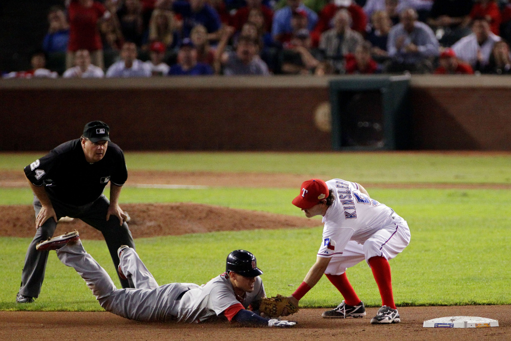 Umpire Jerry Layne looks on as Jon Jay of the St. Louis Cardinals is caught stealing at second base by Ian Kinsler of the Texas Rangers in the seventh inning during Game Five of the MLB World Series at Rangers Ballpark in Arlington on October 24, 2011, in Arlington, Texas.