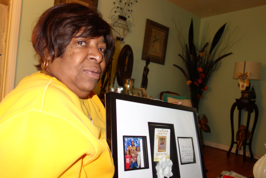 In this file photo, Mahalia Clark holds a framed collage of photos and keepsakes of her great-nephew Ezell Ford. Ford's family has reached a conditional settlement with the city of Los Angeles, according to court records obtained by KPCC.