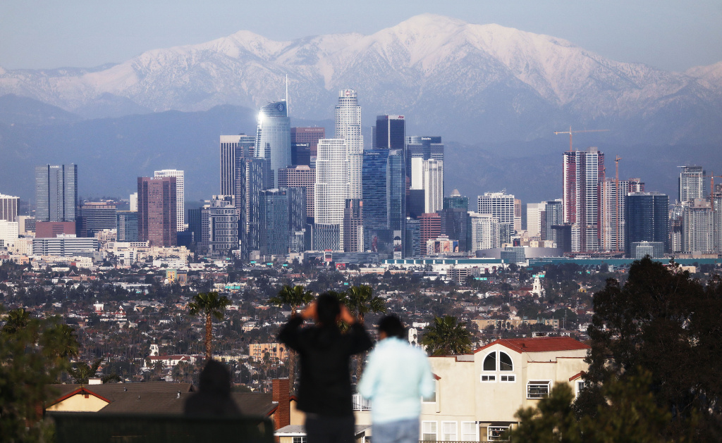 A man takes photos with snow-capped mountains standing behind the skyline of downtown of the city on February 11, 2019 in Los Angeles, California.