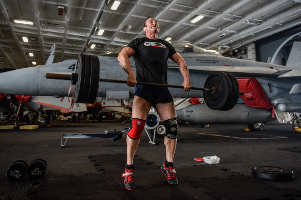 (March. 2, 2018) Lt. Joshua Johnson lifts weights in the hangar bay of the aircraft carrier USS Theodore Roosevelt (CVN 71).