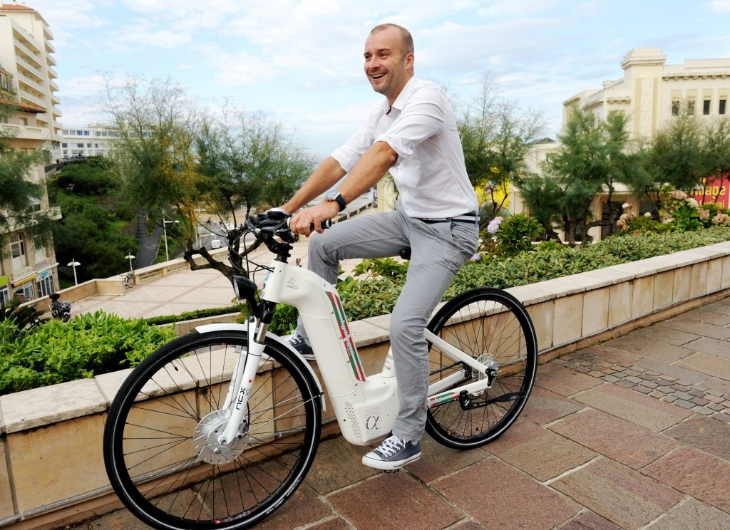 Pragma Industries's CEO Pierre Forte rides an Alpha electric bike in Biarritz, southwestern France.