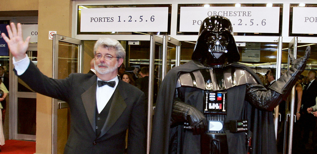 US director George Lucas (L) and Darth Vader wave at spectators at the end of the screening of their film