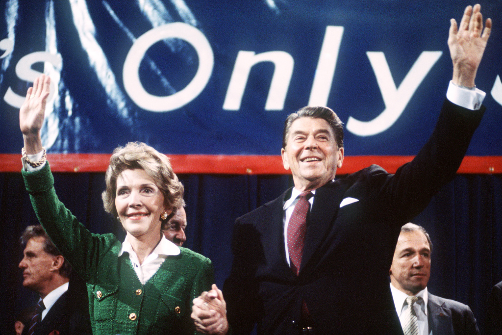 US President and Republican presidential candidate Ronald Reagan and his wife Nancy wave to supporters at an electoral meeting in November 1984, a few days before the U.S. presidential election.