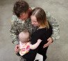 Sergeant Brian Deeds hugs his wife Nicole and daughter Clara, 18 months, after returning from a year-long deployment in Afghanistan, at Pope Air Force base March 16, 2010 in Fort Bragg, North Carolina.