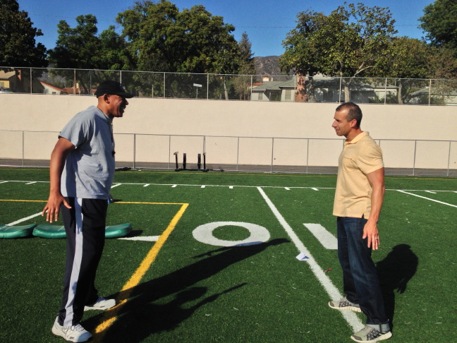 A Martinez braces for the inevitable against Dave Marks, the coach of the Glendale Tornadoes pop warner football team.