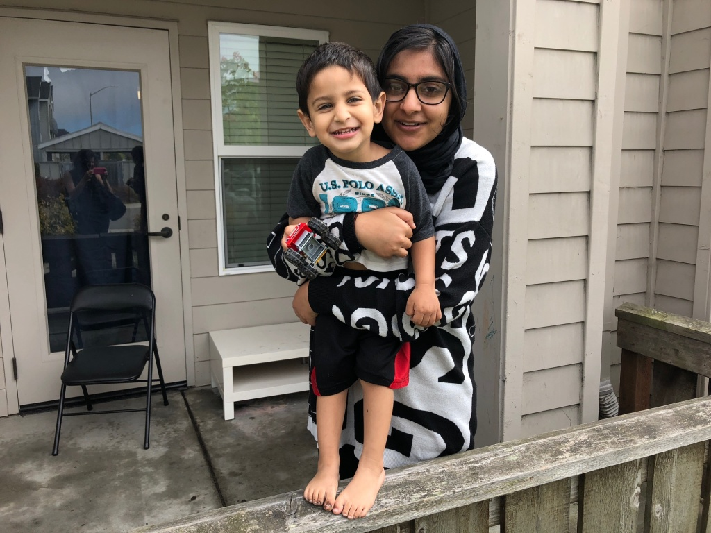 Sadia Kahn with her son Hashim outside their new apartment in University Village.