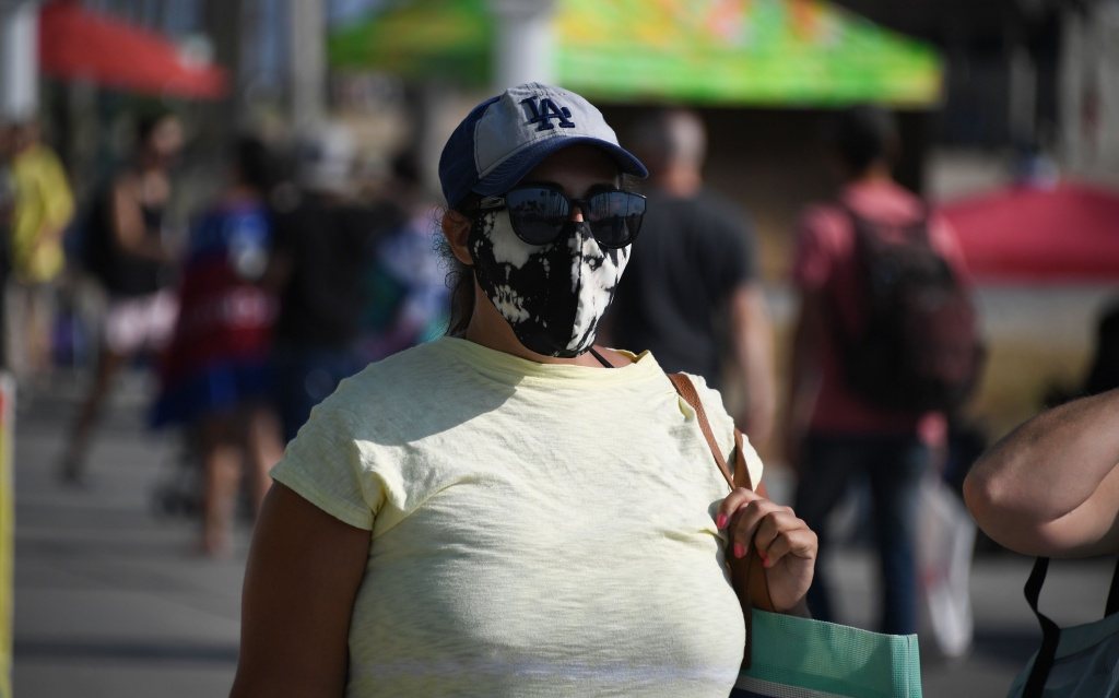 A woman wearing a facemask walks on the boardwalk as many come to the beach to escape the heat wave in Venice Beach, California on September 4, 2020.