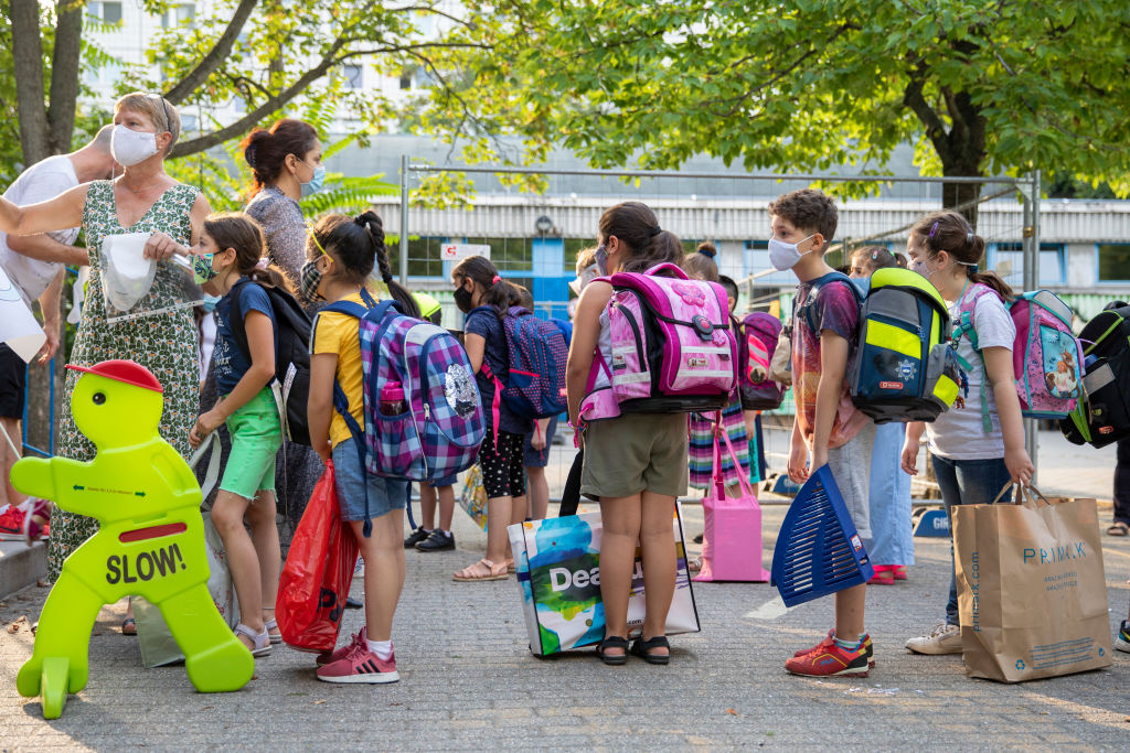Children wearing protective face masks arrive for the first day of classes of the new school year at the GuthsMuths elementary school during the coronavirus pandemic on August 10, 2020 in Berlin, Germany.
