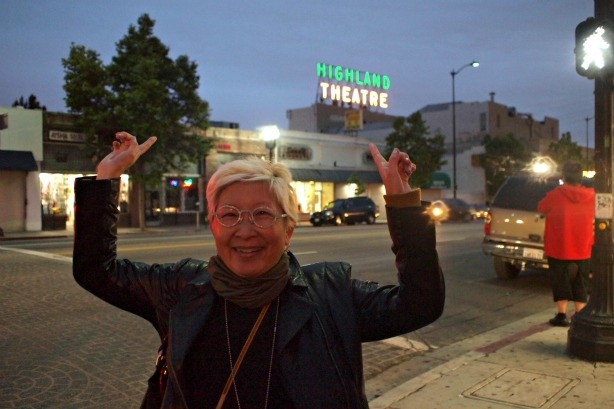 Amy Inouye points to the newly re-lit Highland Theatre sign minutes after the ceremony took place.