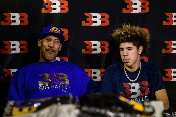 LaVar Ball (L), father of basketball player LiAngelo Ball and the owner of the Big Baller brand, sits with his other son LaMelo Ball (R) during a promotional event in Hong Kong on November 14, 2017. LiAngelo Ball and UCLA basketball teammates Cody Riley and Jalen Hill were arrested on November 7 in Hangzhou.